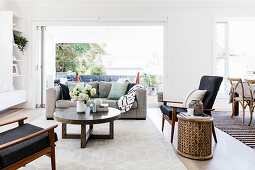 Gray upholstered sofa with cushions, round coffee table, armchair and side table in front of an open patio door in a bright living room