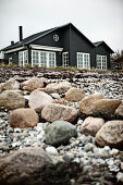 View from shingle beach to black wooden house with lattice windows