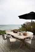 Wooden table and chairs with fur rugs on terrace with sea view