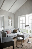 Living room in shades of grey in wooden house with open roof structure
