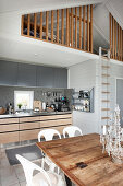 Multifunctional interior in natural shades with bedroom on gallery in holiday home