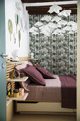 Double bed with bed linen in berry shades, grey-green wallpaper and mobile