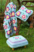Crocheted blanket, cushion and footstool with floral motifs