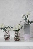 Ranunculus in concrete-effect vase handmade from milk carton and glass vases