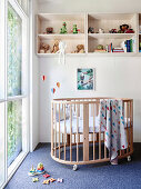 Baby cot and shelf in front of a floor-to-ceiling window in the children's room, toys on the carpet