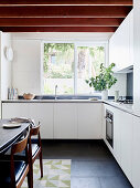 White fitted kitchen with wooden beam ceiling