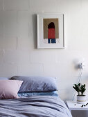 Bed and bedside table in front of white wall with picture in bedroom