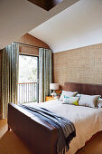 Double bed with leather headboard and footboard, textile wallpaper and French window in the bedroom