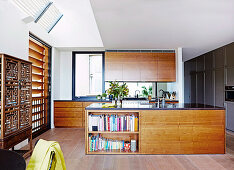 Elegant kitchen unit with walnut wood fronts and kitchen island in an open living room