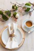 Place setting, cup of coffee and handmade concrete Easter eggs wrapped in moss decorating table