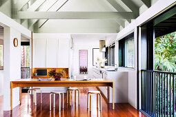White fitted kitchen and wooden table with stools in open living room
