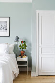 Geranium on bedside table against pale blue wall in bedroom