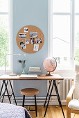 Round cork pinboard above desk on trestles