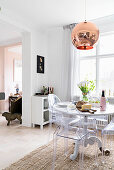 Round dining table and designer chairs in front of window in open-plan kitchen