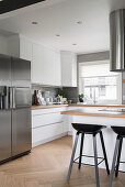 White fitted kitchen with stainless steel fridge, island counter and bar stools
