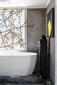 Free-standing bathtub below window decorated with branches