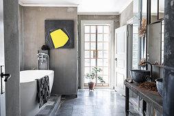 Vintage washstand with metal basins, free-standing bathtub and artwork in bathroom