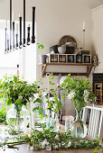 Vases of flowers and twigs on table in kitchen-dining room