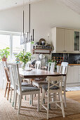 Various chairs around dining table in country-house kitchen