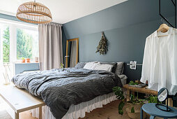 Bed with valance against blue-grey wall in bedroom