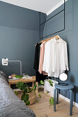 Clothes rail hung from ceiling against grey walls