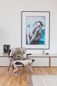Fur blanket on leather armchair in front of console table below photographic artwork