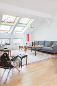 Grey sofa, coffee table, leather armchair and footstool in attic living room