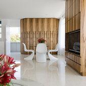 Weiße Designerstühle um Glastisch vor Holzverkleidung, im Vordergrund Fernsehregal