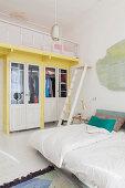 Fitted wardrobes below loft bed in bedroom