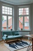 Two-seater sofa below window