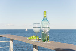 Bottle of wine, glasses and grapes on terrace railing with sea view