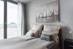 Bedroom in pale shades with maritime artwork above bed and view of beach