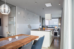 Dining table, kitchen island and couch in elongated open-plan interior
