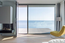 Uninterrupted sea view through floor-to-ceiling windows and across wooden deck without balustrade
