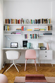 Two chairs below designer String shelves with integrated desk