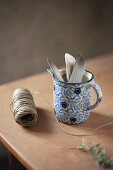 Feathers in blue-and-white jug and reel of twine on table
