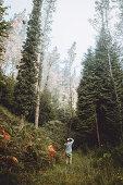 Ein Mann fotografiert im herbstlichen Wald