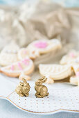 Two golden bunnies on plate in front of Easter biscuits