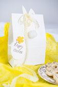 Osterhase mit Spitzenborte an einer Geschenktüte auf gelbem Papier