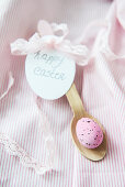 Pink Easter egg on wooden spoon with tag