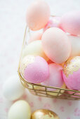Pink eggs with gold leaf in wire basket