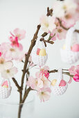 Easter eggs in crocheted baskets hung from flowering branch of fruit tree