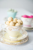 Pale yellow quail eggs in vintage collectors' cup