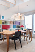 Designer lamp above dining table in front of shelving with colourful compartment doors