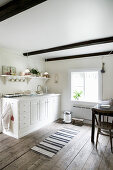 White kitchen counter in rustic kitchen-dining room with wooden floor