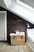 Wicker basket next to bed below sloping ceiling with skylight
