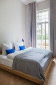 Doppelbett vor Terrassentür im Altbau-Schlafzimmer