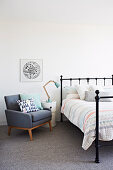 Gray upholstered armchair and bedside table next to bed in bedroom