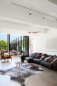 Gray sofa set with cushions and coffee table on animal fur rug in front of patio door