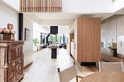 Fitted kitchen with wooden fronts and kitchen island in an open living room